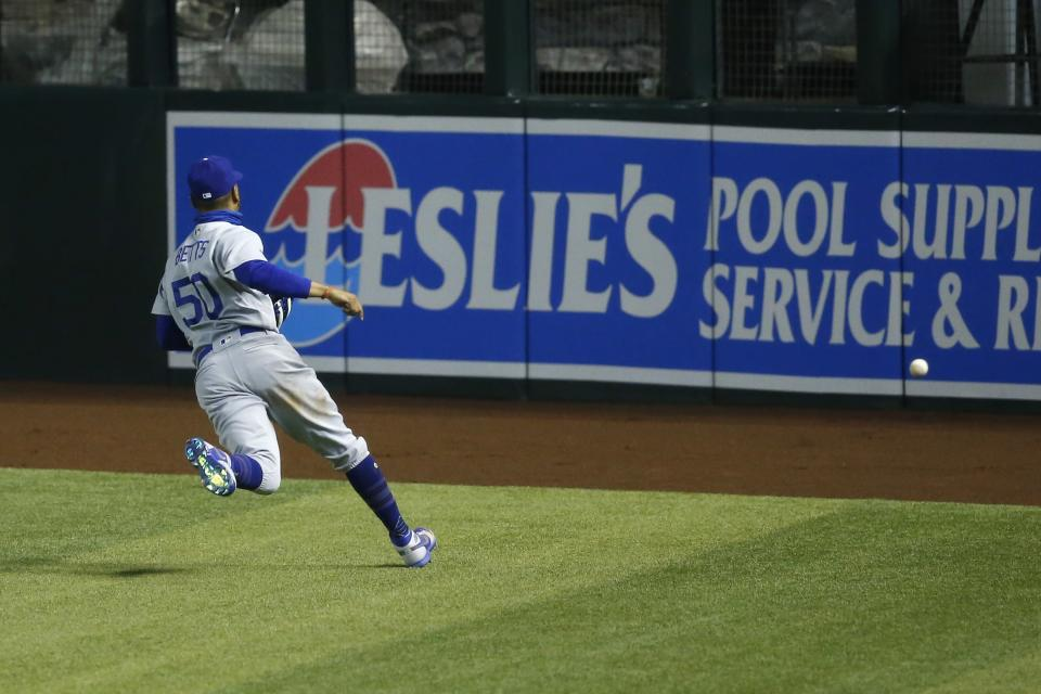 Los Angeles Dodgers center fielder Mookie Betts tries to chase down a three-run double hit by Arizona Diamondbacks' Christian Walker during the eighth inning of a baseball game Friday, July 31, 2020, in Phoenix. (AP Photo/Ross D. Franklin)