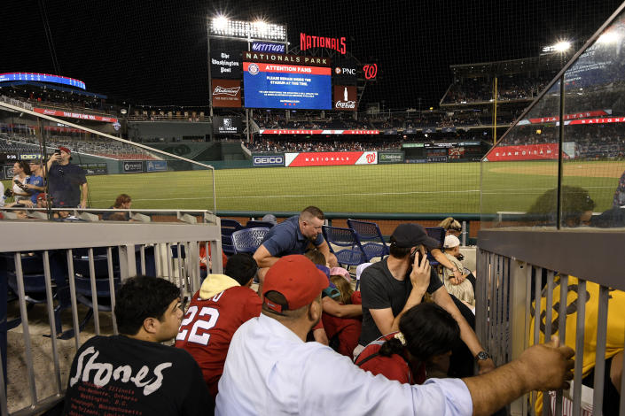 Spectators take cover during a stoppage in play due to an incident near the ballpark during the sixth inning of a baseball game between the Washington Nationals and the San Diego Padres, Saturday, July 17, 2021, in Washington. (AP Photo/Nick Wass)
