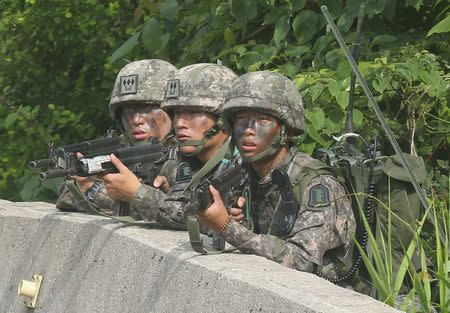 South Korean soldiers take position during a search and arrest operation as troops standoff with a conscript soldier who shot and killed five comrades in Goseong June 23, 2014. REUTERS/Hwang Gwang-mo/Yonhap