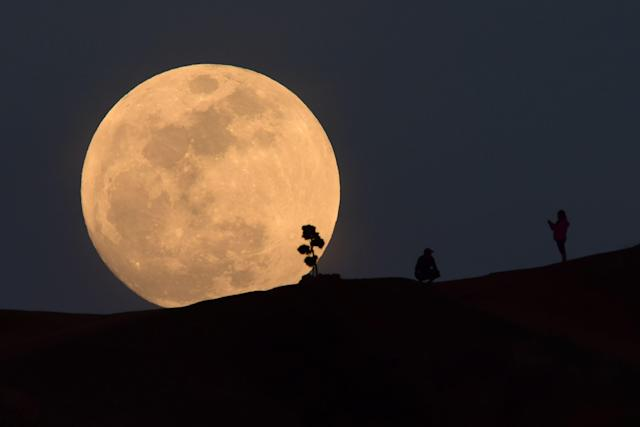 <p>A person poses for a photo as the moon rises over Griffith Park in Los Angeles, California, on Jan. 30, 2018. (Photo: Robyn Beck/AFP/Getty Images) </p>