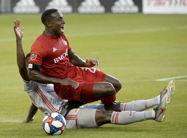 Toronto FC midfielder Richie Laryea (22) takes a rough tackle from New York Red Bulls defender Kemar Lawrence during the first half of an MLS soccer match Wednesday, July 17, 2019, in Toronto. (Nathan Denette/The Canadian Press via AP)