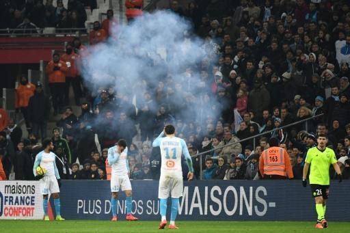 Marseille players Jordan Amavi, Kevin Strootman and Kostas Mitroglou react after a firecracker explodes beside the pitch during their team's defeat against Lille on Friday