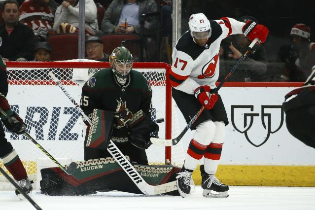 Arizona Coyotes goaltender Darcy Kuemper (35) moves into position to make a save as New Jersey Devils right wing Wayne Simmonds (17) tries to redirect the puck during the second period of an NHL hockey game, Saturday, Dec. 14, 2019, in Glendale, Ariz. (AP Photo/Ross D. Franklin)