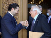 In this photo released by Lebanese government, Lebanese Prime Minister-Designate Saad Hariri, left, greets European Union foreign policy chief Josep Borrell with a fist bump, in Beirut, Lebanon, Saturday, June. 19, 2021. Borrell berated Lebanese politicians for delays in forming a new Cabinet, warning the union could impose sanctions on those behind the political stalemate in the crisis-hit country. (Dalati Nohra/Lebanese Official Government via AP)