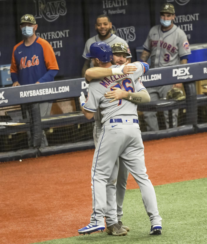 New York Mets' Pete Alonzo hugs Patrick Mazeika (76) outside the dugout after his solo home run off Tampa Bay Rays reliever Diego Castillo during the sixth inning of a baseball game Sunday, May 16, 2021, in St. Petersburg, Fla. (AP Photo/Steve Nesius)