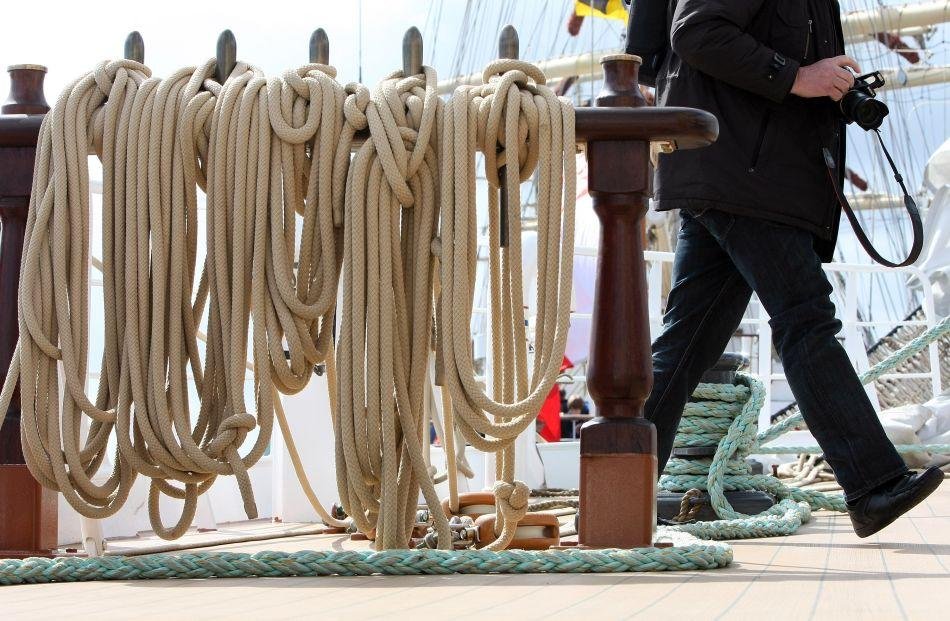 A visitor walks by rope tied to sails on board the German tall ship Alexander von Humboldt II.