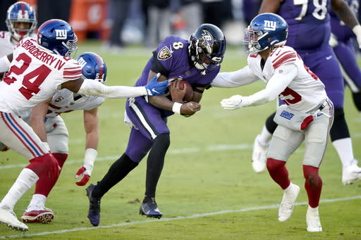Baltimore Ravens quarterback Lamar Jackson (8) runs with the ball as New York Giants cornerback James Bradberry (24) and safety Xavier McKinney (29) try to stop him during the first half of an NFL football game, Sunday, Dec. 27, 2020, in Baltimore. (AP Photo/Gail Burton)