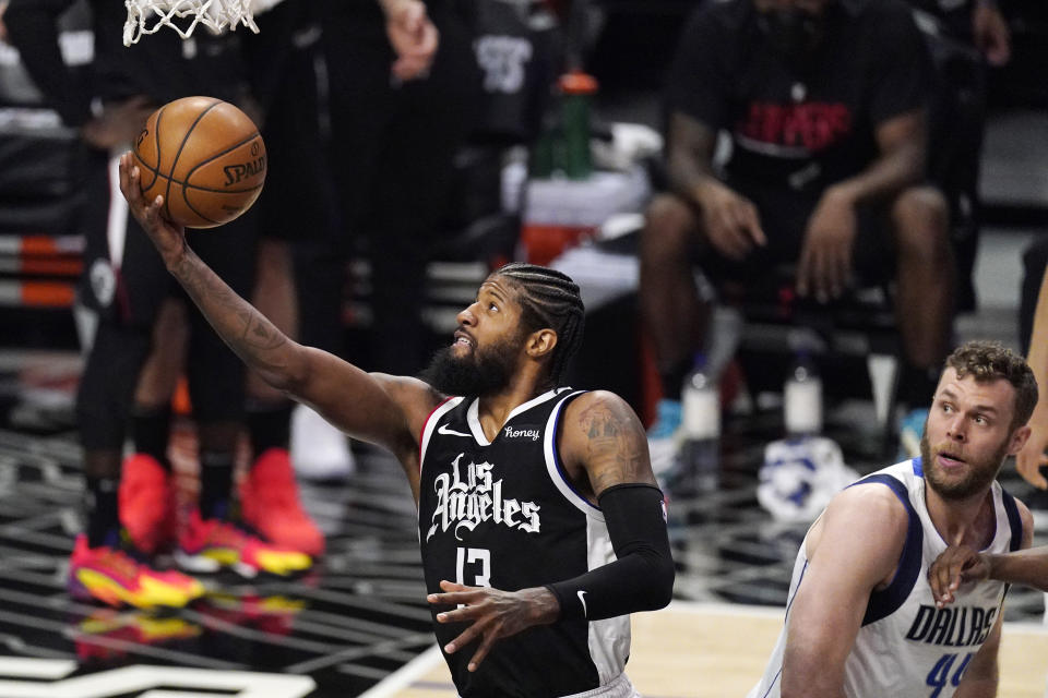 Los Angeles Clippers guard Paul George, left, shoots as Dallas Mavericks forward Nicolo Melli watches during the first half in Game 1 of an NBA basketball first-round playoff series Saturday, May 22, 2021, in Los Angeles. (AP Photo/Mark J. Terrill)
