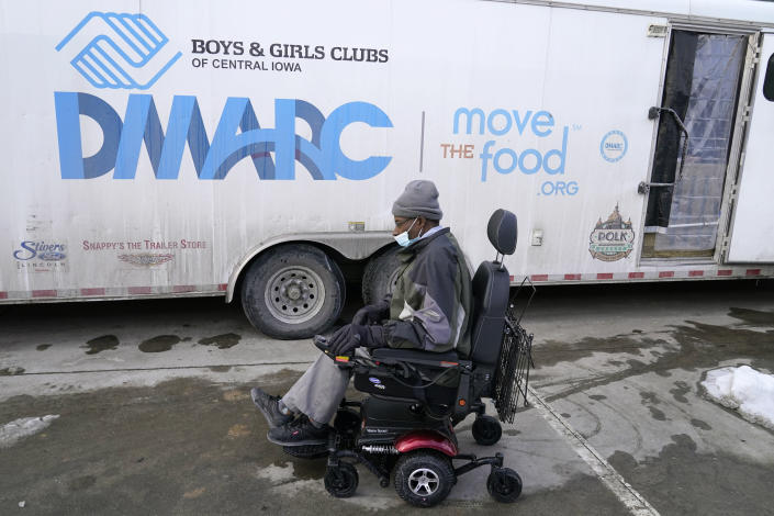 Thomas Washington, of Des Moines, Iowa, arrives at a Des Moines Area Religious Council mobile food pantry stop to pick up a Farmers to Families Food Box, Thursday, Feb. 18, 2021, in Des Moines, Iowa. Agricultural groups and anti-hunger organizations are pushing the Biden administration to continue the Farmers to Families Food Box program launched by President Donald Trump that spent $6 billion to prevent farmers from plowing under food and instead provide it to millions of Americans left reeling by the coronavirus pandemic. (AP Photo/Charlie Neibergall)