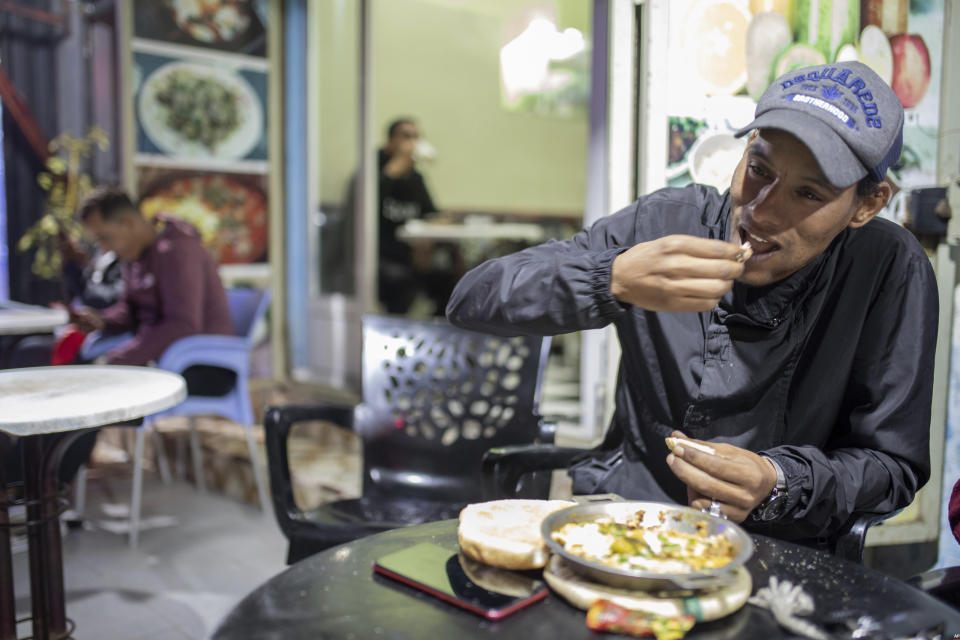 A man eats, in a restaurant in central Dakhla, Western Sahara, Monday, Dec. 21, 2020. U.S. plans to open a consulate in Western Sahara mark a turning point for the disputed and closely policed territory. U.S. recognition of Morocco's authority over the land frustrates indigenous Sahrawis seeking independence. But others see the future U.S. consulate as a major boost for Western Sahara cities like Dakhla. (AP Photo/Mosa'ab Elshamy)