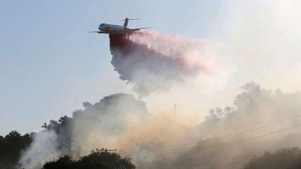 PHOTO: A plane drops fire retardant on the Maria Fire in the early morning in Santa Paula, Calif., Nov. 1, 2019. (Daniel Dreifuss/Reuters)