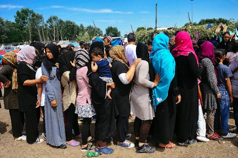 Women queue to receive food at a migrant camp situated on the Serbia-Hungary border in Horgos on July 8, 2016