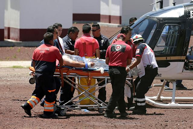 <p>Paramedics wheel a stretcher carrying a man injured due to fireworks explosions toward a helicopter in the municipality of Tultepec, on the outskirts of Mexico City, Mexico July 5, 2018. (Photo: Daniel Becerril/Reuters) </p>