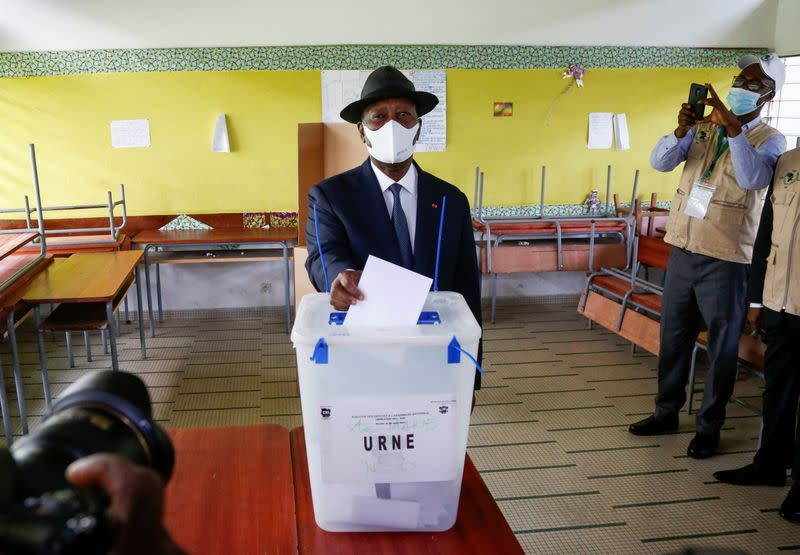 Ivory Coast President Alassane Ouattara casts his vote at a polling station during the legislative election in Abidjan