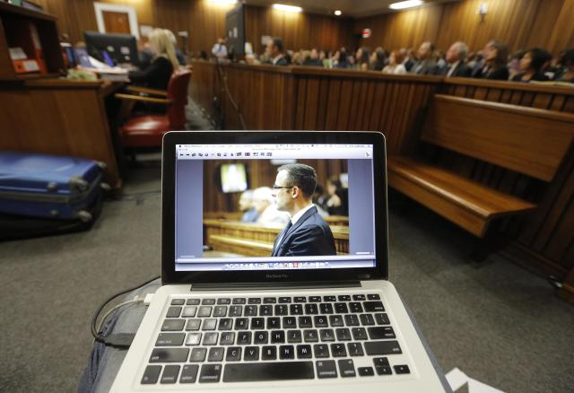 Oscar Pistorius is viewed on a laptop as he sits in the dock in court in Pretoria, South Africa, Friday, March 14, 2014 on the tenth day of proceedings. Pistorius is charged with the shooting death of his girlfriend Reeva Steenkamp on Valentines Day in 2013. (AP Photo/Kim Ludbrook, Pool)