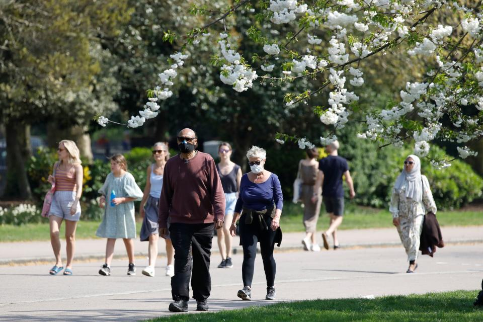 A couple wear facemasks as they take their daily excercise in Victoria Park, east London on April 11, 2020 as warm weather tests the nationwide lockdown due to the novel coronavirus COVID-19 and the long Easter weekend begins. - The disease has struck at the heart of the British government, infected more than 60,000 people nationwide and killed over 8,000, with a daily death toll in England of 866 reported on April 10. (Photo by Tolga AKMEN / AFP) (Photo by TOLGA AKMEN/AFP via Getty Images)