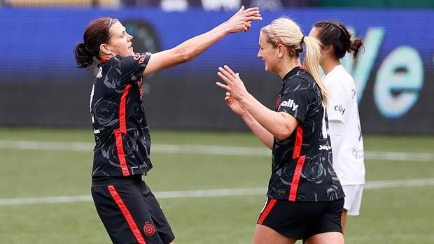 Canada's Christine Sinclair, left, celebrates her 60th goal in all NWSL competitions on Saturday. She scored another after the match headed to penalty kicks to help the Portland Thorns defeat Gotham FC in the Challenge Cup final in Portland, Ore. (Steph Chambers/Getty Images - image credit)