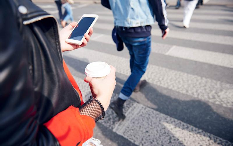 A recent case has highlighted the potential danger of crossing a road while looking at your phone - Cultura RF