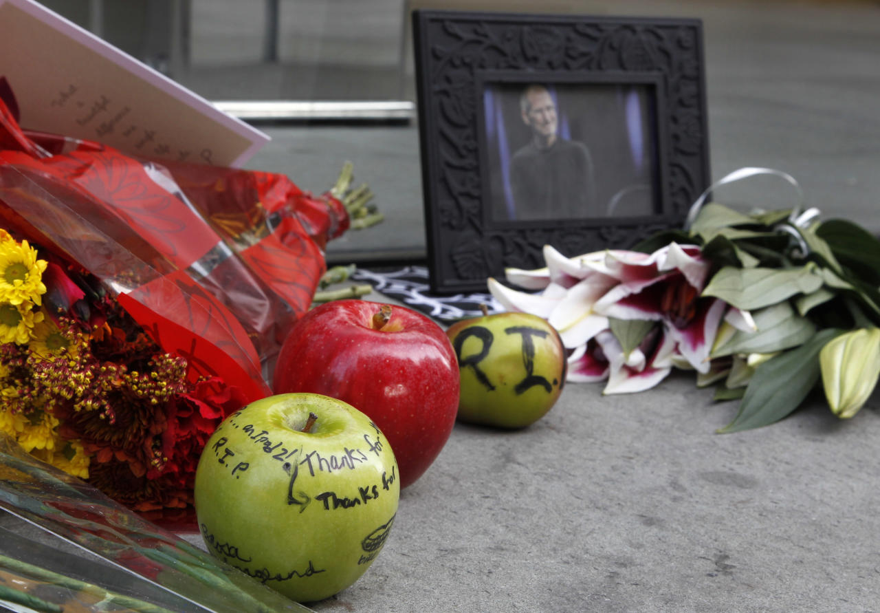 A photograph of Apple co-founder Steve Jobs near apples with messages written on them form part of a memorial in front of an Apple store in Boston, Thursday, Oct. 6, 2011. Jobs died Wednesday at 56. (AP Photo/Steven Senne)