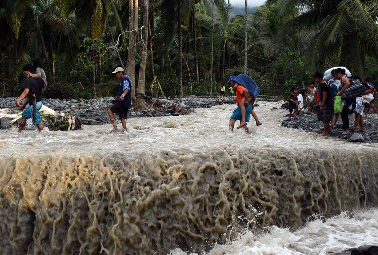 Philippine residents cross a damaged road destroyed by Typhoon Bopha in the village of Andap