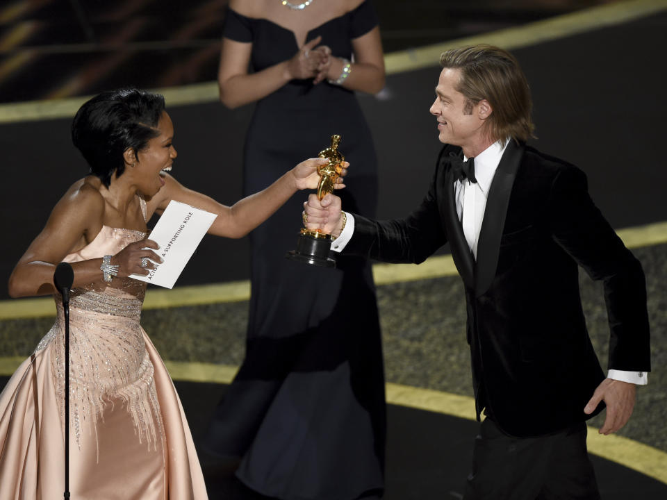 """Regina King, left, presents Brad Pitt with the award for best performance by an actor in a supporting role for """"Once Upon a Time in Hollywood"""" at the Oscars on Sunday, Feb. 9, 2020, at the Dolby Theatre in Los Angeles. (AP Photo/Chris Pizzello)"""