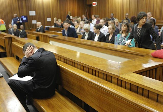 Oscar Pistorius blocks his ears inside the high court on the second day of his trial in Pretoria, South Africa, Tuesday, March 4, 2014. Pistorius is charged with murder for the shooting death of his girlfriend, Reeva Steenkamp, on Valentines Day in 2013. (AP Photo/Kim Ludbrook, Pool)