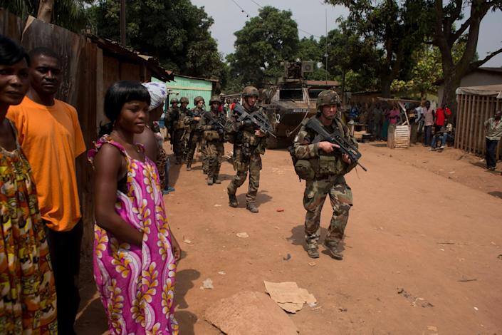 French soldiers arrive outside the house of an ex-Seleka general, during an operation to secure an area of the Miskine neighborhood, in Bangui, Central African Republic, Thursday, Dec. 26, 2013. The spokesman for an African Union peacekeeping force says six Chadian peacekeepers were killed and 15 were wounded, after being attacked Wednesday. (AP Photo/Rebecca Blackwell)