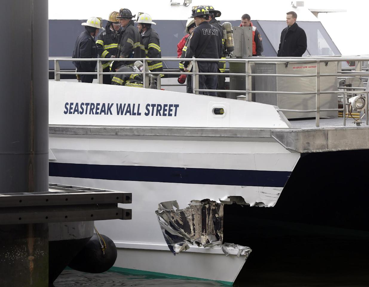 New York City firefighters walk the deck of the Seastreak Wall Street ferry in New York, Wednesday, Jan. 9, 2013. The ferry from Atlantic Highlands, N.J., banged into the mooring as it arrived at South Street in lower Manhattan during morning rush hour, injuring as many as 50 people, at least one critically, officials said.(AP Photo/Richard Drew)