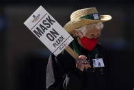 FILE - In this March 16, 2021, file photo, an usher holds a sign to remind fans to wear masks during a spring training baseball game between the Oakland Athletics and the Arizona Diamondbacks in Scottdale, Ariz. The Republican-controlled Arizona Senate voted Monday, March 29, to rescind its mandatory mask policy, and the House speaker made the same move on his own authority. (AP Photo/Ashley Landis, File)