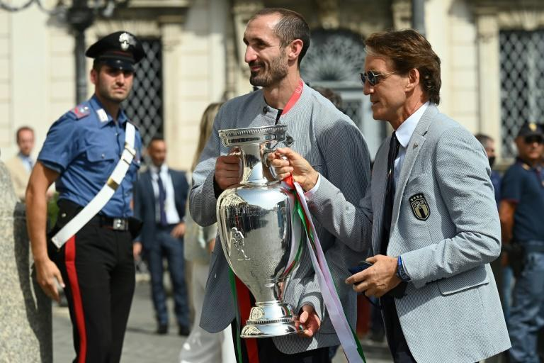 Italy coach Roberto Mancini (R) and captaom Giorgio Chiellini carry the Euro 2020 trophy at the Quirinale presidential palace in Rome.