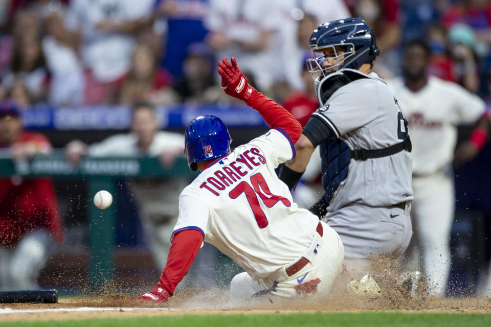 Philadelphia Phillies' Ronald Torreyes (74) is safe at home on an RBI-single by Jean Segura before New York Yankees catcher Gary Sanchez, right, can make the catch during the 10th inning of a baseball game, Saturday, June 12, 2021, in Philadelphia. (AP Photo/Laurence Kesterson)