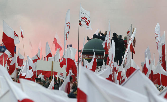 Members of radical right-wing groups light up flares during a march by tens of thousands of people and hosted by President Andrzej Duda that marked 100 years since Poland regained independence in Warsaw, Poland, Sunday, Nov. 11, 2018.(AP Photo/Czarek Sokolowski)