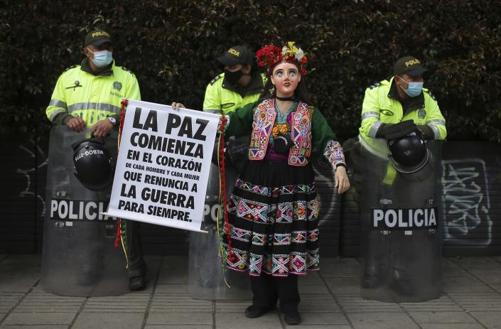 """A woman dressed in a traditional Mexican dress and mask holds a sign that reads in Spanish """"Peace begins in the heart of every man and woman to renounce war forever."""" as police stand guard on the sidelines of an anti-government march in Bogota, Colombia, Wednesday, May 19, 2021. Colombians have taken to the streets for weeks across the country after the government proposed tax increases on public services, fuel, wages and pensions. (AP Photo/Ivan Valencia)"""