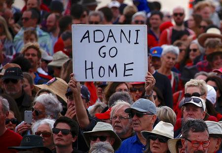 A protester holds a sign as he participates in a national Day of Action against the Indian mining company Adani's planned coal mine project in north-east Australia, at Sydney's Bondi Beach in Australia