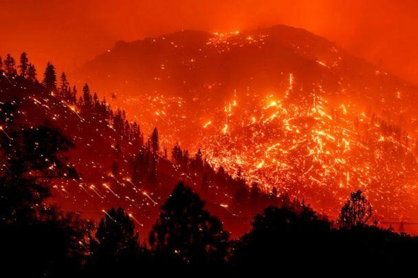 PHOTO: Embers light up the hills as the Dixie Fire burns near Milford in Lassen County, Calif., August 17, 2021, in a long exposure photograph.  (Noé Berger / AP)