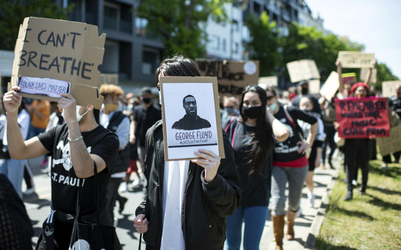 "People protest in Berlin, Germany, Sunday, May 31, 2020 after the violent death of the African-American George Floyd by a white policeman in the USA against racism and police violence, among other things with a sign ""I can't breathe"". (Bernd von Jutrczenka/dpa via AP)"