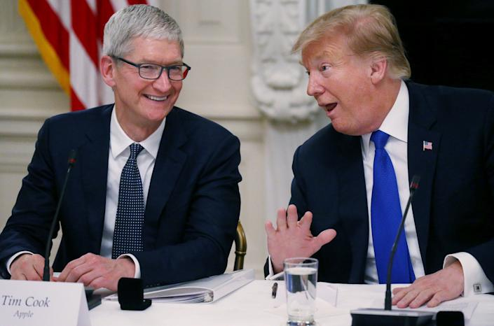 Tim Cook laughs with Donald Trump at the White House in 2019 (REUTERS)