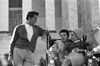 <p>Elizabeth Taylor sits on her husband Eddie Fisher's lap while he visits her on the set of <em>Cleopatra </em>in Rome. The couple are seen talking to Taylor's costar, Richard Burton, whom the actress would eventually leave Fisher to marry. </p>