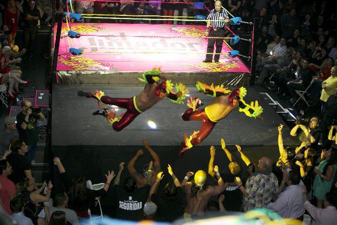 In this Wednesday, Feb. 12, 2014 photo, wrestling duo The Crazy Chickens fly over the ropes and into the audience during the Lucha VaVoom Valentine's show of Lucha Libre Mexican wrestling and Burlesque performances at the Mayan Theatre downtown Los Angeles. The esoteric hybrid of American burlesque and Mexican wrestling is an outrageous hit.(AP Photo/Damian Dovarganes)