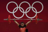 Loa Dika Toua of Papa New Guinea competes in the women's 49kg weightlifting event, at the 2020 Summer Olympics, Saturday, July 24, 2021, in Tokyo, Japan. (AP Photo/Luca Bruno)