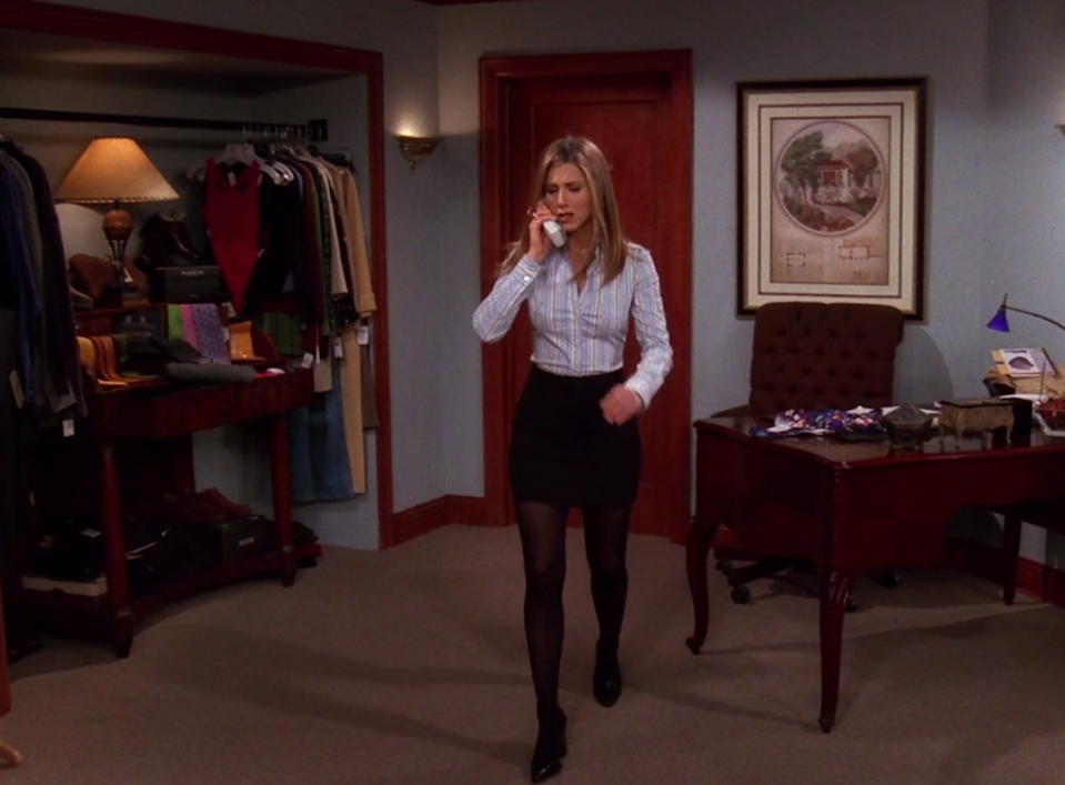 Rachel wearing small boots, tights, a mini skirt, and a long-sleeve button up