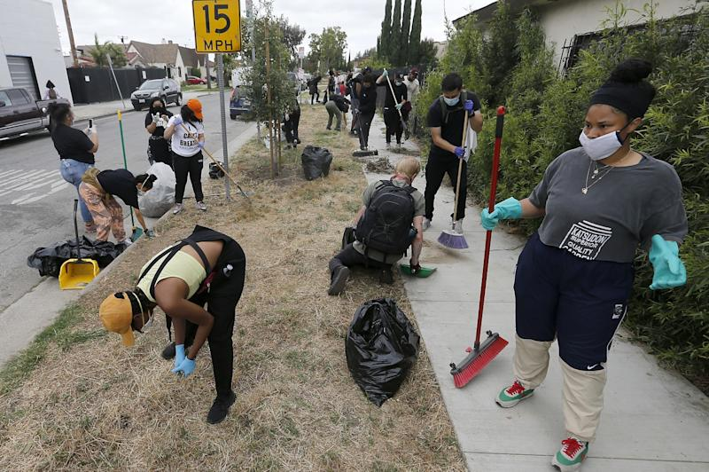 Volunteers pull weeds along in South Los Angeles during community cleanup on Friday, June 5, 2020.