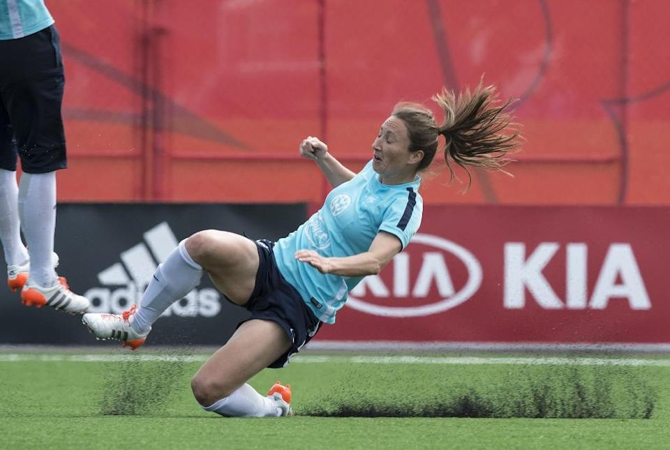 France's Gaetane Thiney slips as she trains on the artificial turf pitch in Ottawa on June 18, 2015 (AFP Photo/Nicholas Kamm)