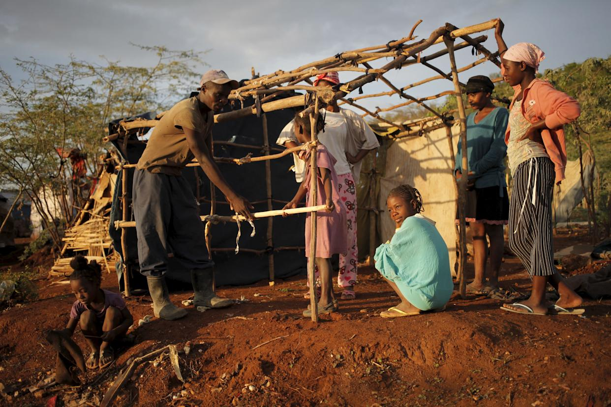 A man ties sticks to build a makeshift tent at a refugee camp for Haitians returning from the Dominican Republic on the outskirts of Anse-a-Pitreson Sept. 7, 2015.