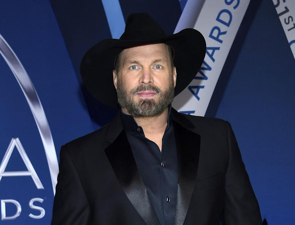 Garth Brooks in a black suit with a black cowboy hat
