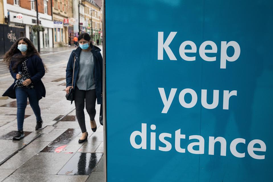 Members of the public wearing face coverings to help prevent the spread of the coronavirus pass a Keep your distance COVID-19 public information display on 4 October 2020 in Slough, United Kingdom. Slough Borough Council confirmed on 2nd October that its coronavirus infection rate is the highest in the south of England and Slough MP Tan Dhesi asked Health Secretary Matt Hancock in Parliament whether the local test centre in Montem Lane could be reverted to permit walk-in and drive-in visits without an appointment. (photo by Mark Kerrison/In Pictures via Getty Images)