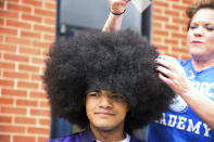 """In this photo provided by Gregg Gelmis, Kieran Moïse, 17, has his 19-inch hair cut and donated to the nonprofit Children With Hair Loss, which provides human hair replacements to children and teenagers facing medically-related hair loss, on Saturday, May 29, 2021, in Huntsville, Ala. Moïse also launched a fundraiser through St. Jude Children's Research Hospital in memory of classmate Josh Quist, who died from cancer. So far their charity, """"Kieran's Curls for Cancer,"""" has raised $35,000. (Courtesy of Gregg Gelmis via AP)"""