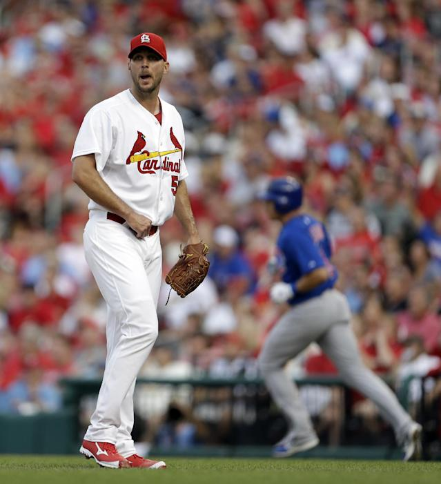 St. Louis Cardinals starting pitcher Adam Wainwright, left, watches as a solo home run by Chicago Cubs' Cody Ransom, right, clears the left field wall during the first inning of a baseball game on Tuesday, June 18, 2013, in St. Louis. (AP Photo/Jeff Roberson)