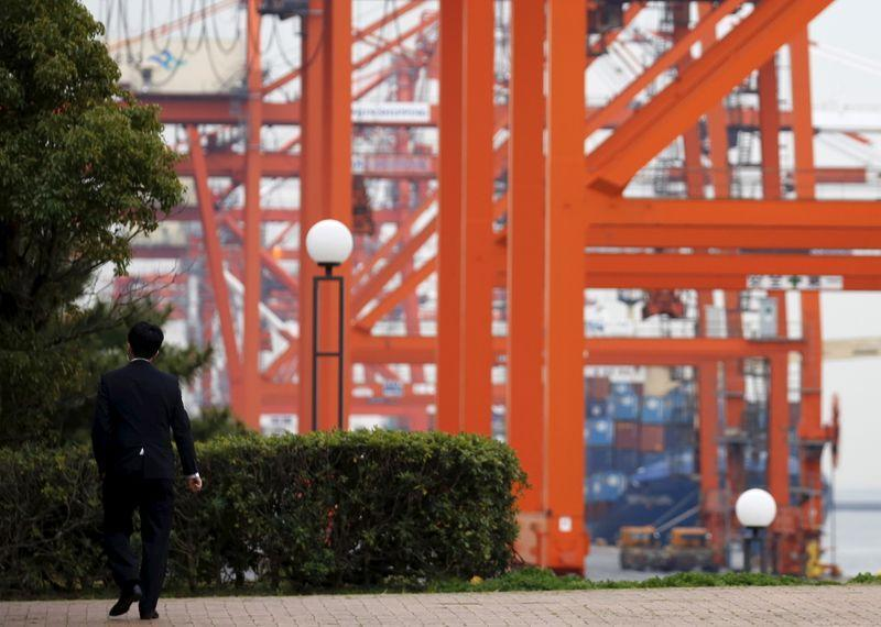 A businessman walks near a cargo area at a port in Tokyo