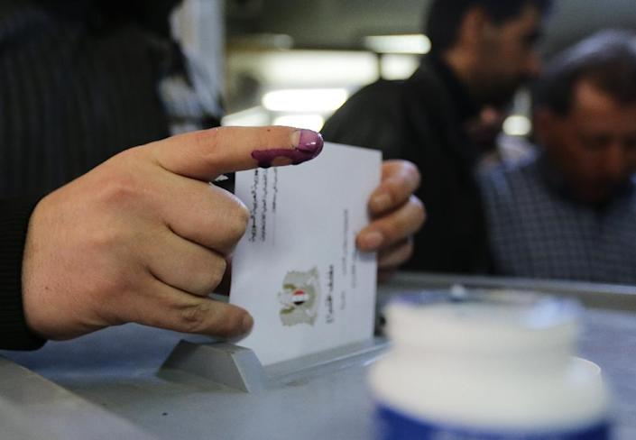 Syrians cast their votes for the parliamentary elections at a polling station in Damascus, on April 13, 2016 (AFP Photo/Louai Beshara)